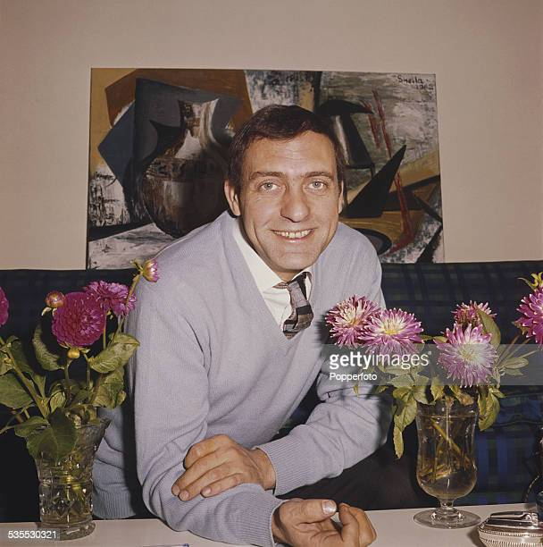 English actor Harry H Corbett who plays the character of Harold Steptoe in the television sitcom Steptoe And Son posed at a table with two vases of...