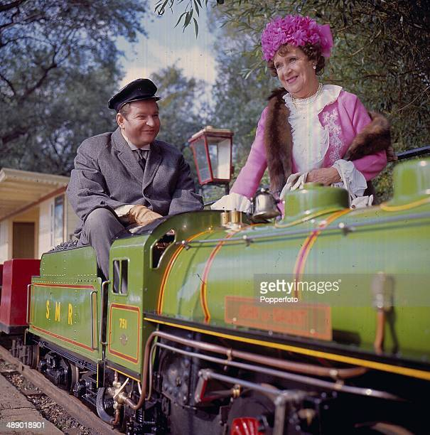 English actor Hugh Manning and actress Kathleen Harrison pictured on a miniature train in a scene from the television series 'Mrs Thursday' in 1966