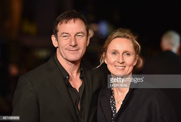 "English actor Jason Isaacs and his wife Emma Hewitt pose for photographers on the red carpet as they arrive for the European premier of ""Fury"" during..."