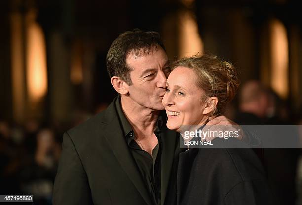English actor Jason Isaacs and his wife Emma Hewitt pose for photographers on the red carpet as they arrive for the European premier of Fury during...