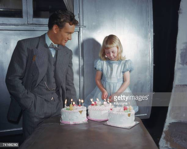 English actor John Mills with his co-star and daughter Juliet on the set of 'So Well Remembered', directed by Edward Dmytryk, 1947.
