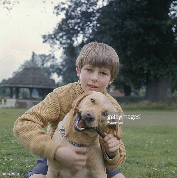 1968 English actor John MoulderBrown pictured holding a dog in a scene from the television drama series 'Weavers Green' in 1968
