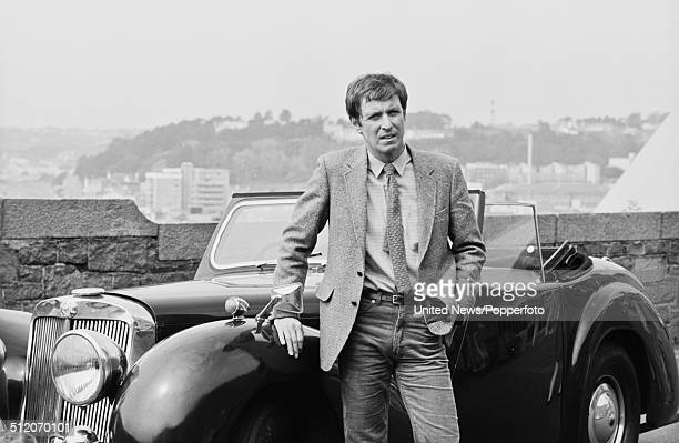 English actor John Nettles who appears as Jim Bergerac in the television drama series Bergerac posed beside a vintage Triumph Roadster car on 30th...