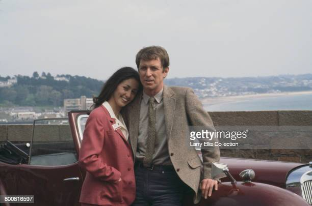 English actor John Nettles who appears in character as Jim Bergerac in the television drama series 'Bergerac' posed together with French actress...
