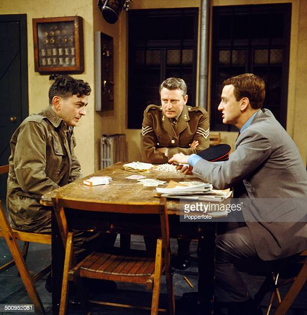 English actor John Thaw pictured sitting on right at a table with the actors William Lucas and Patrick Bedford in a scene from the television drama...