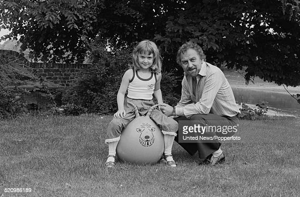 English actor John Thaw pictured with his daughter sitting on a space hopper in a garden in London on 2nd June 1980