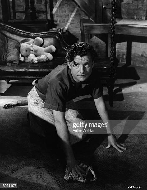 English actor Kenneth More cleans up the puppy's mess in a scene from the domestic comedy 'Raising A Riot' directed by Wendy Toye for British Lion /...