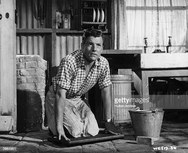 English actor Kenneth More on his knees on the floor in a scene from the domestic comedy 'Raising A Riot' directed by Wendy Toye for British Lion /...