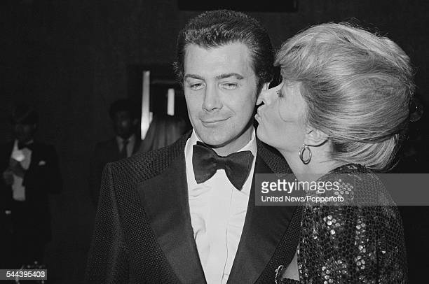 English actor Lewis Collins is kissed by actress Ingrid Pitt at the premiere of the film 'Who Dares Wins' in London on 26th August 1982