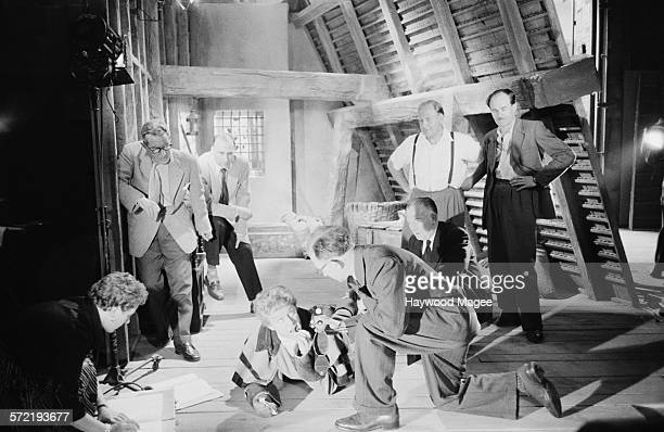 English actor Marius Goring with crew members during filming of the ITV series 'The Adventures of the Scarlet Pimpernel' at Elstree Studios...