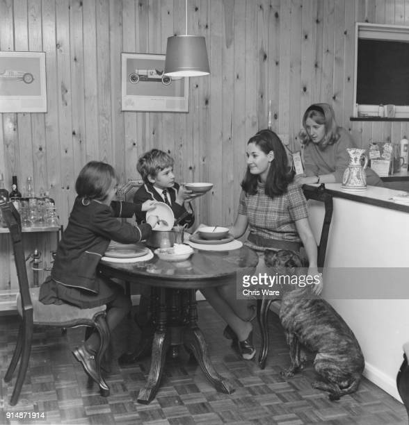 English actor Mark Lester young star of the musical film version of 'Oliver' asks for a second helping at his home UK 1967 With him are his...