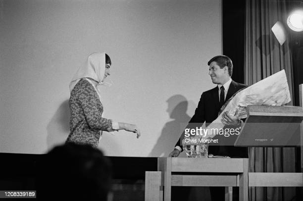 English actor Matthew Scurfield and American comedian, actor, singer, filmmaker and humanitarian Jerry Lewis , holding a bouquet of flowers, on stage...