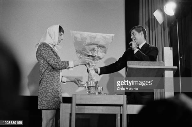 English actor Matthew Scurfield handing a bouquet of flowers to American comedian actor singer filmmaker and humanitarian Jerry Lewis while on stage...
