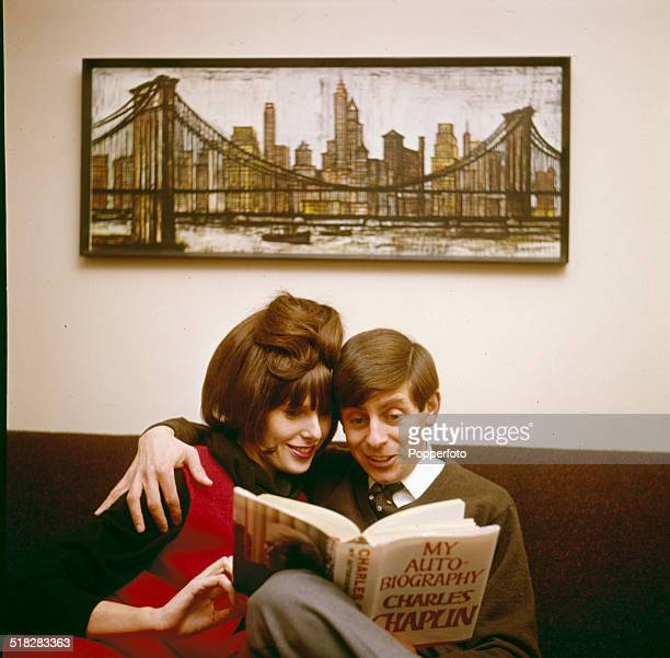 English actor Melvyn Hayes pictured with his wife actress Rosalind Allen reading a Charlie Chaplin autobiography at home in 1965