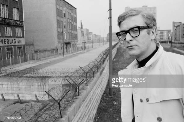 English actor Michael Caine at the Berlin Wall in Berlin, Germany, during the filming of the Harry Palmer spy drama 'Funeral in Berlin', 12th April...