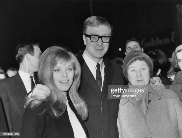 English actor Michael Caine brings his mother Ellen and girlfriend Edina Ronay to the UK premiere of his film 'The Ipcress File' 19th March 1965