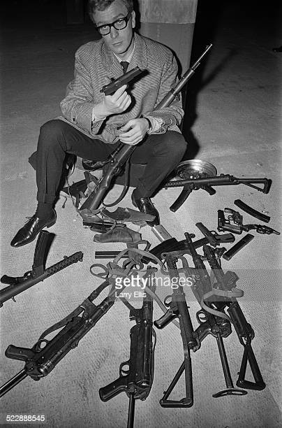 English actor Michael Caine sitting with an array of guns during the filming of 'The Ipcress File' 13th October 1964