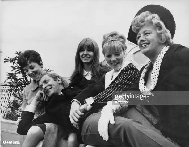English actor Michael Caine star of the film 'Alfie' surrounded by his female costars 5th July 1965 From left to right the actresses are Vivien...