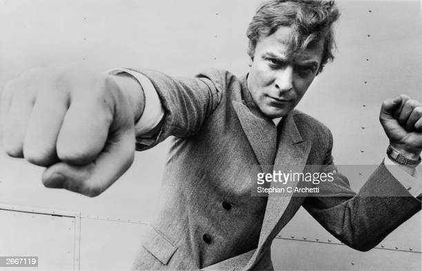 English actor Michael Caine, throwing a punch, August 1965.