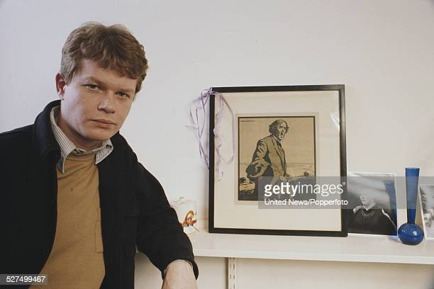 English actor Michael Cochrane who appears in the television series Wings pictured standing by a mantlepiece beside a framed print of Sir Henry...