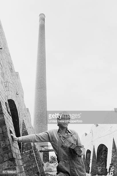 English actor Michael Crawford dressed in dungarees and a hard hat stands in front of a tall chimney stack in character as Frank Spencer during...