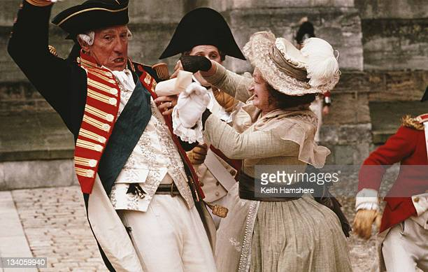 English actor Nigel Hawthorne as King George III is attacked by actress Janine Duvitski as wouldbe assassin Margaret Nicholson in a scene from the...