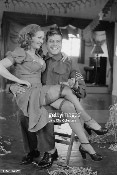 English actor Oliver Reed pictured dressed in character as a British Army Sergeant with actress Jenny LeeWright during shooting of the film The...