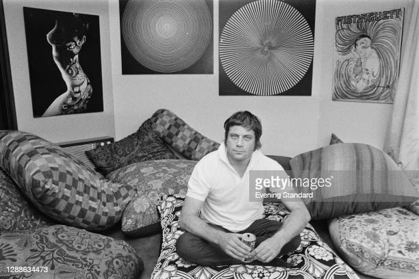 English actor Oliver Reed , UK, 1971. He is drinking a can of Coca-Cola, and on the wall to the right is a poster of French actress and singer...