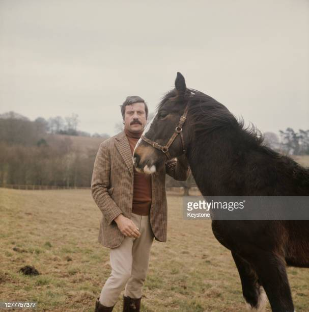 English actor Oliver Reed with a horse in the countryside near his home, UK, circa 1973.