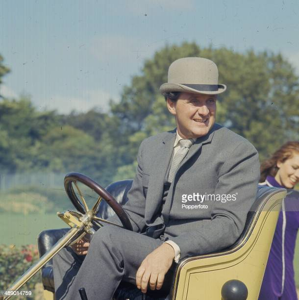 English actor Patrick Macnee as 'John Steed' drives a vintage car on the set of the television series 'The Avengers' in 1967.