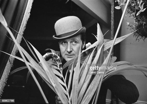 English actor Patrick Macnee concealed behind a houseplant, 20th May 1965.