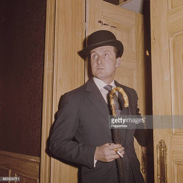 English actor Patrick Macnee pictured in character as John Steed, wearing his trademark suit and bowler hat in a scene from the television drama...