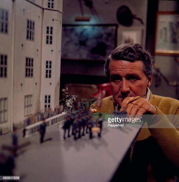 English actor Patrick Macnee pictured painting model soldiers in a scene from the television drama 'The Long Nightmare' in 1966.