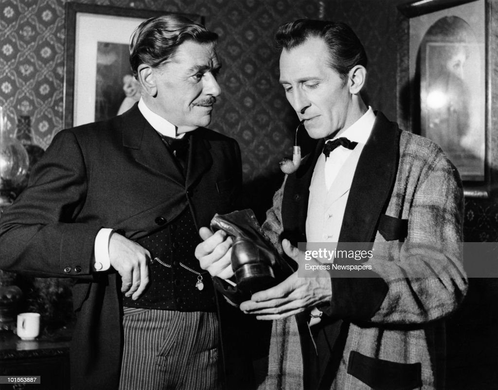 English actor Peter Cushing (1913 - 1994) as fictional detective Sherlock Holmes with Andre Morell (1909 - 1978) as Doctor Watson in a scene from 'The Hound of the Baskervilles', 1959.