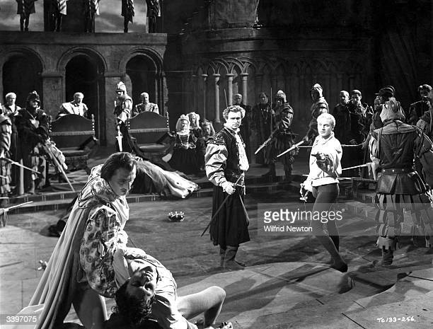English actor producer and director Laurence Olivier playing Hamlet in his film version of Shakespeare's work He is involved in a sword fight with...