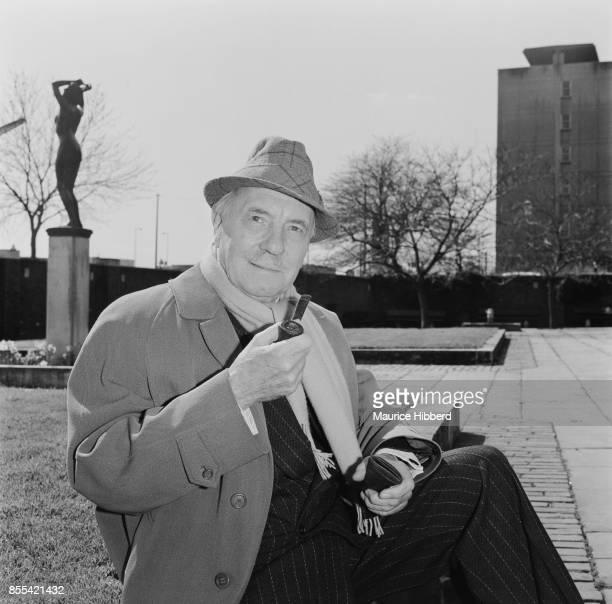 English actor Ralph Richardson sits outside while smoking a pipe UK 7th April 1978