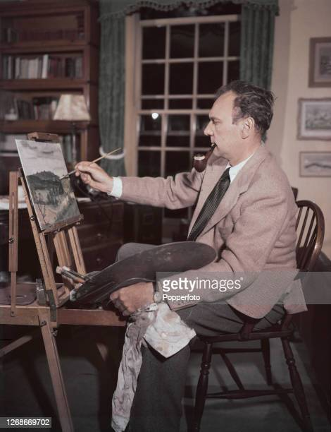 English actor Ralph Richardson smokes a pipe as he paints a landscape painting in the study of his house in Hampstead London in 1951