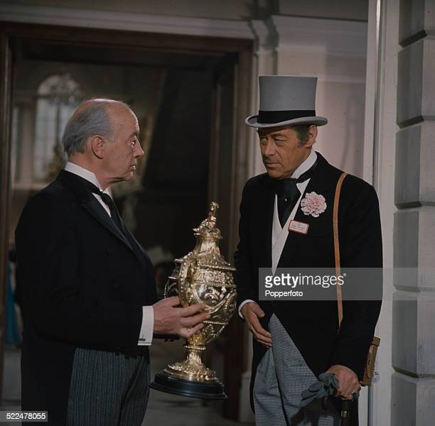 English actor Rex Harrison is presented with a gold cup in a scene from the film 'The Yellow RollsRoyce' in 1964