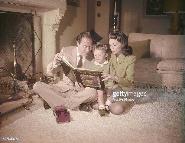 English actor Rex Harrison with his second wife actress Lilli Palmer and their threeyearold son Carey perusing a book of Van Gogh paintings circa...