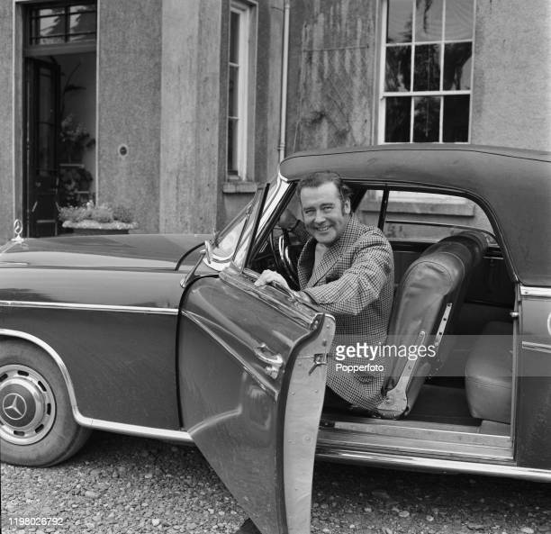 English actor Richard Greene seated in the driver's seat of his Mercedes car outside his house Borleagh Manor near Gorey in County Wexford Ireland in...