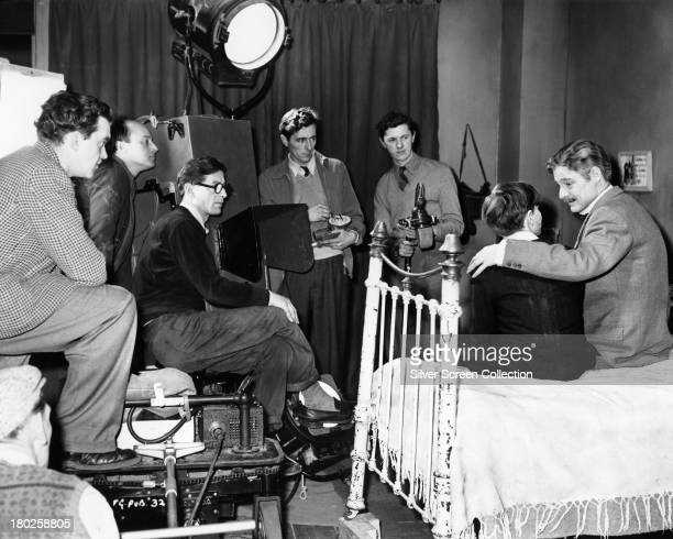 English actor Robert Donat performing on the set of 'The Magic Box' with a film crew including cinematographer Jack Cardiff and director John...