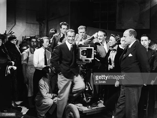 English actor Robert Douglas stands on a camera dolly at the opening of Pinewood Studios in Buckinghamshire 30th September 1936 With him are director...