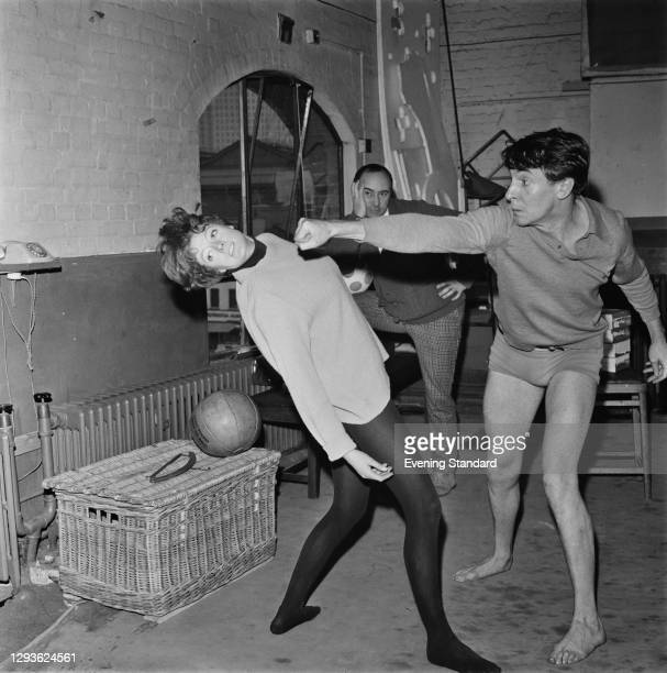 English actor Robert Stephens throws a stage punch at actress Maggie Smith, watched by theatre director John Dexter , during a rehearsal for a...