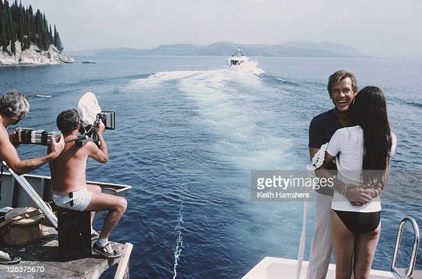 English actor Roger Moore as 007 with French actress Carole Bouquet as Melina Havelock on the set of the James Bond film 'For Your Eyes Only'...