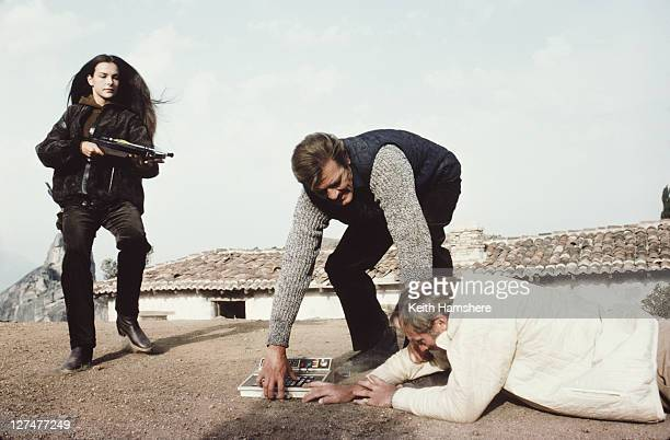 English actor Roger Moore as 007 with French actress Carole Bouquet as Melina Havelock and English actor Julian Glover as Aristotle Kristatos in a...
