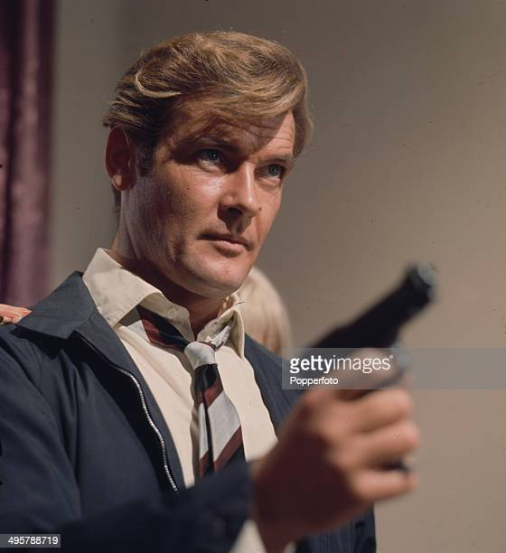 English actor Roger Moore as Simon Templar holds a hand gun in a scene from the television series 'The Saint' in 1968