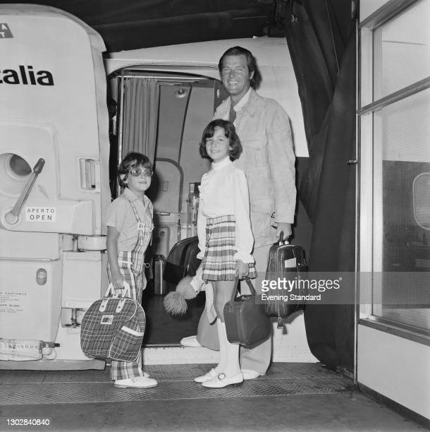 English actor Roger Moore boards an Alitalia aircraft with his children Deborah and Geoffrey, UK, 2nd August 1972. Both children followed him into...