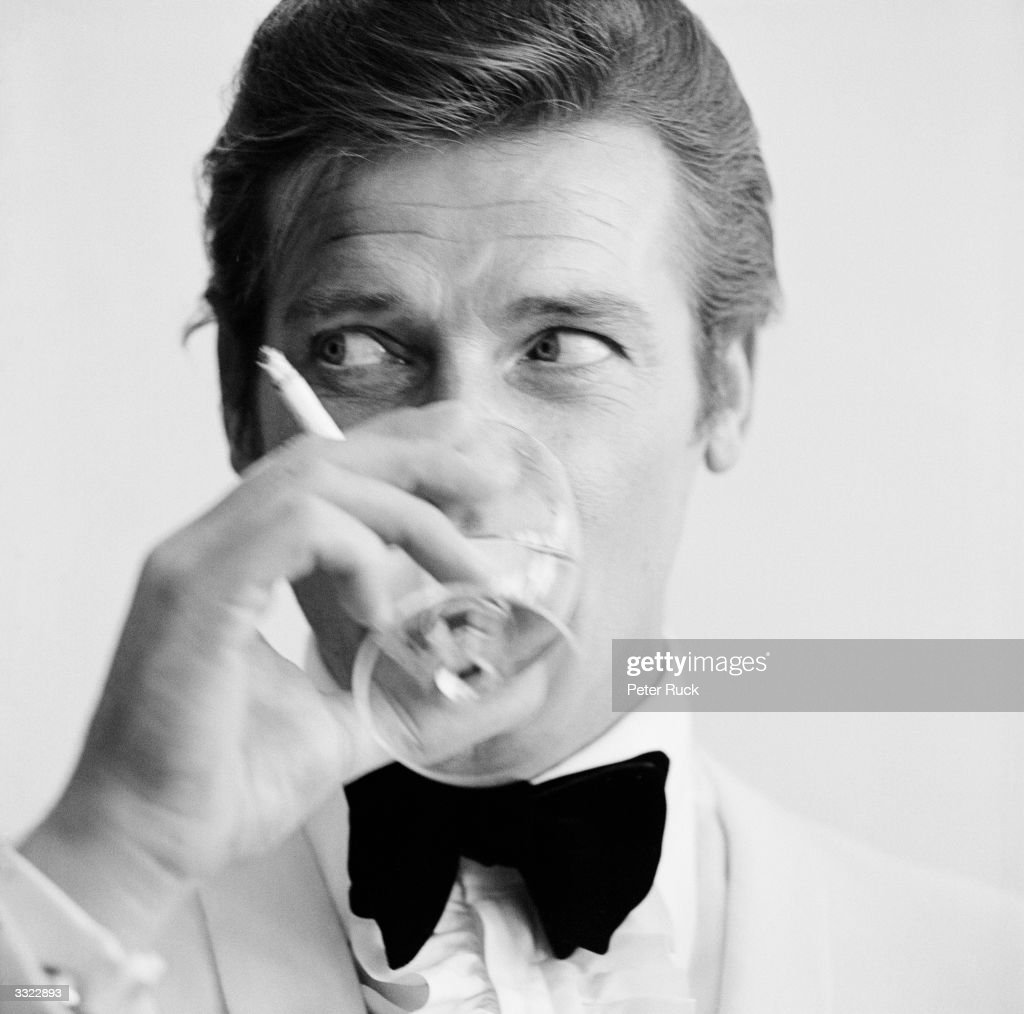 English actor Roger Moore, downs a Martini, 17th July 1968. Moore has recently been awarded his second Bravo Otto award for most popular television actor, by German magazine Bravo, for his mystery spy thriller television series, 'The Saint'.