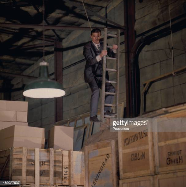 English actor Roger Moore in character as 'Simon Templar' stands half way up a ladder in a scene from the television series 'The Saint' in 1967