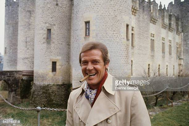 English actor Roger Moore in front of Roquetaillade Castle on the set of 'Sunday Lovers' directed by Bryan Forbes   Location Roquetailiade Castle...